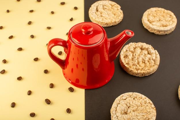 Een bovenaanzicht rode ketel met bruine koffiezaden en crackers