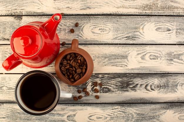 Een bovenaanzicht rode ketel met kopje koffie en bruine koffiezaden op het grijze rustieke bureau drinkt koffiekleur