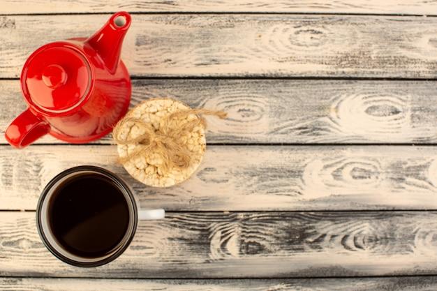Een bovenaanzicht rode ketel met kopje koffie en crackers op het grijze rustieke bureau drinkt koffiekleur