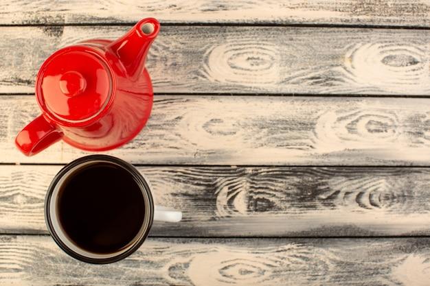 Een bovenaanzicht rode ketel met kopje koffie op het grijze rustieke bureau drinkt koffiekleur