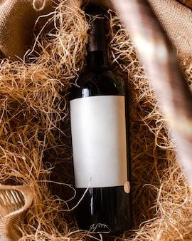 Een bovenaanzicht rode wijn fles rode wijn op het hooi