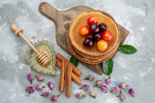 Een bovenaanzicht rond gebakken pannenkoeken en heerlijk met kersen en kaneel op het licht van de cakefruit