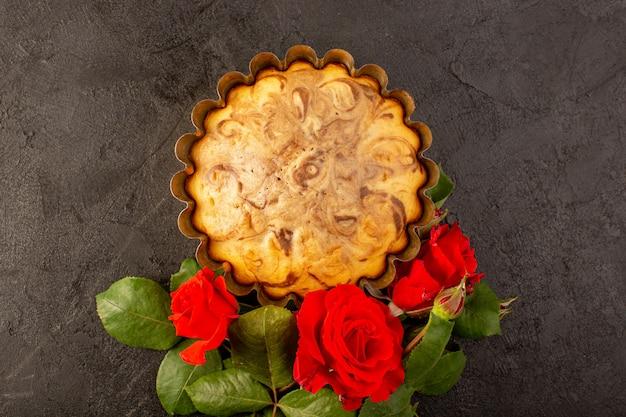 Een bovenaanzicht ronde zoete cake heerlijke en lekkere chocoladetaart in cake pan samen met rode rozen geïsoleerd op de grijze achtergrond suiker thee koekje bakken