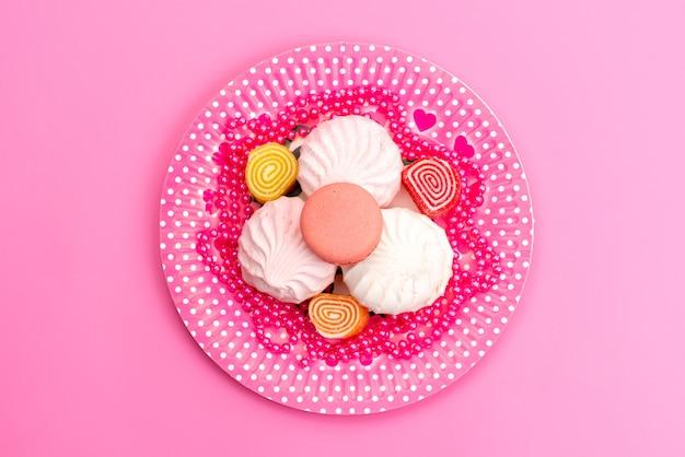 Een bovenaanzicht schuimgebak en marmelade in roze, plaat op roze, cake, koekjes, suikerwerk