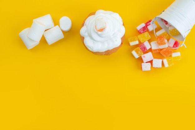 Een bovenaanzicht schuimgebak en marshmallows met marmelade op gele, suikerzoete snoepkleur