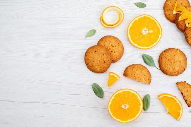 Een bovenaanzicht sinaasappelsmaak koekjes met verse sinaasappelschijfjes fruit koekjeskoekje