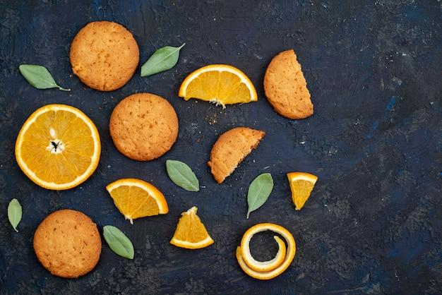 Een bovenaanzicht sinaasappelsmaak koekjes met verse sinaasappelschijfjes op het donkere bureau koekje suiker fruit