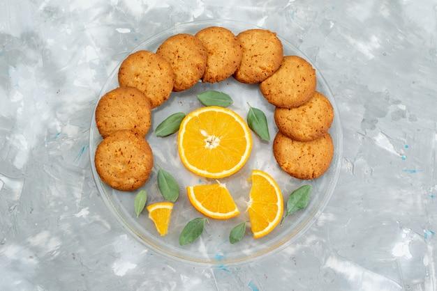Een bovenaanzicht sinaasappelsmaak koekjes met verse stukjes sinaasappel binnen plaat cookie koekje suiker fruit
