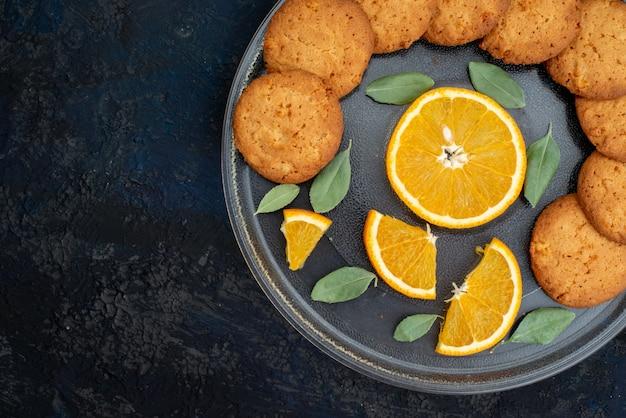 Een bovenaanzicht sinaasappelsmaak koekjes met verse stukjes sinaasappel binnen plaat op de donkere achtergrond cookie koekje suiker citrus
