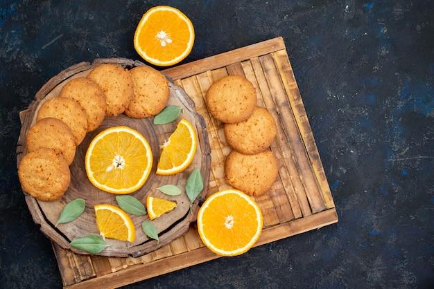 Een bovenaanzicht sinaasappelsmaak koekjes met verse stukjes sinaasappel op de donkere achtergrond koekjessuiker