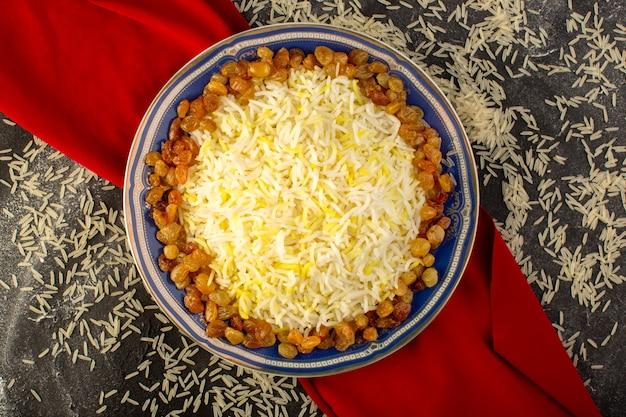 Een bovenaanzicht smakelijke pilaf met olie en gedroogde rozijnen in plaat met rauwe rijst op het donkere oppervlak