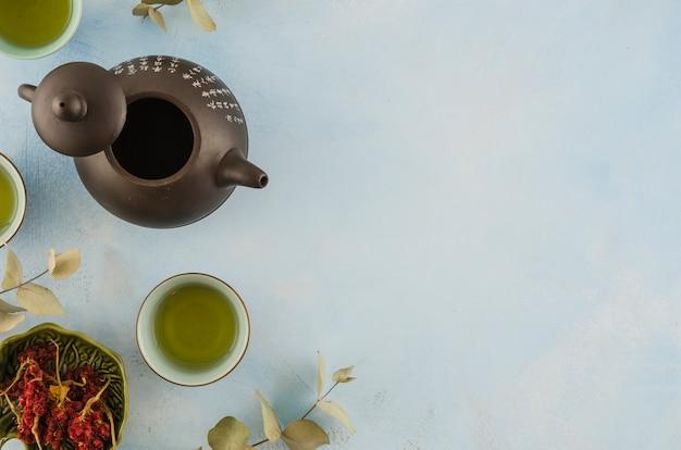 Een bovenaanzicht van aziatische traditionele theepot en theekopjes met kruiden op witte achtergrond