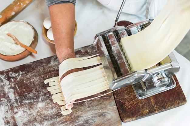 Een bovenaanzicht van bakker snijden rauwe deeg in tagliatelle op pasta machine