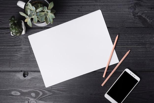 Een bovenaanzicht van blanco papier met twee kleurpotloden en smartphone op houten tafel