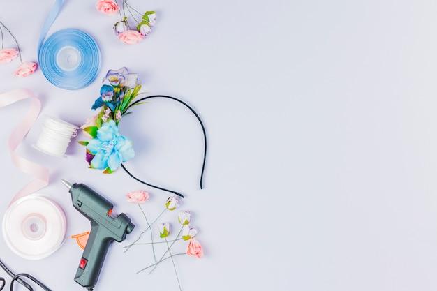Een bovenaanzicht van blauw en wit lint; kunstbloem; lijmpistool voor het maken van haarband op witte achtergrond