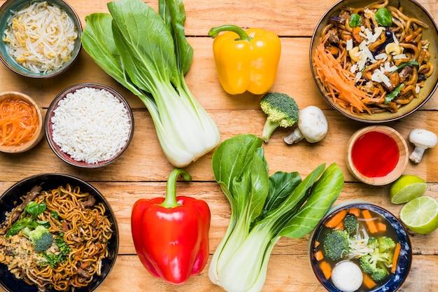 Een bovenaanzicht van bokchoy; paprika; broccoli; paddestoel; citroen met thais eten op houten bureau