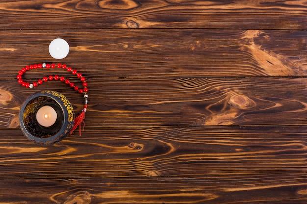 Een bovenaanzicht van brandende kaars in de houder met heilige parels op houten bureau