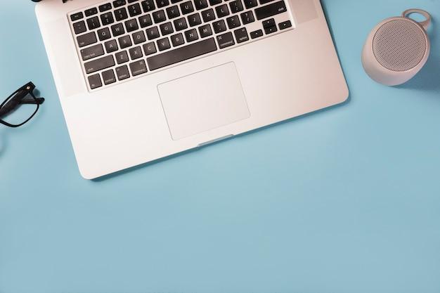 Een bovenaanzicht van brillen; bluetoothspreker en laptop op blauwe achtergrond