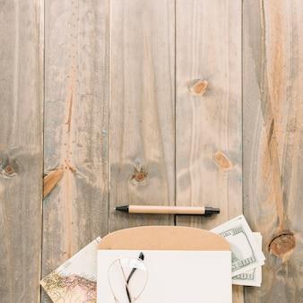 Een bovenaanzicht van brillen; kladblok; valuta; kaart en pen op houten plank achtergrond