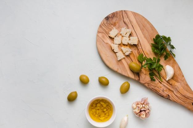 Een bovenaanzicht van brood; peterselie; knoflook en kom met gegoten olijfolie geïsoleerd op een witte achtergrond