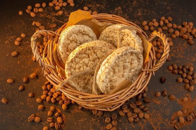 Een bovenaanzicht van bruine koffiezaden met een mand met crackers over de hele bruine tafel
