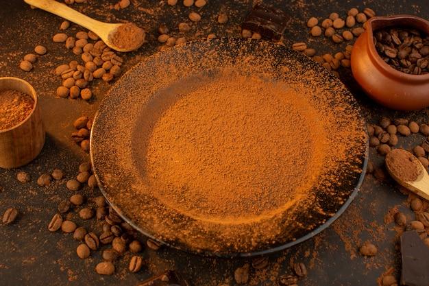 Een bovenaanzicht van bruine koffiezaden samen met een zwarte plaat vol koffiepoeder met choco-repen overal op de bruine tafel