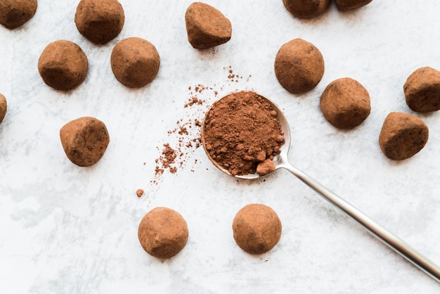 Een bovenaanzicht van cacao ballen op witte gestructureerde achtergrond