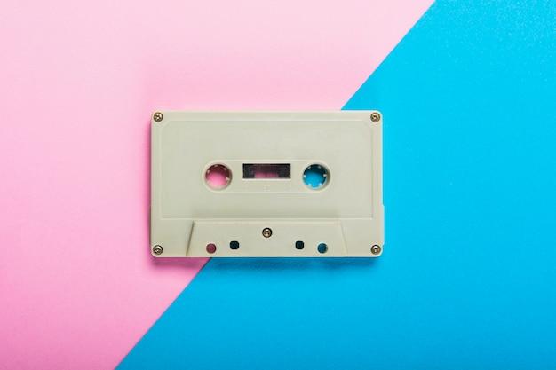 Een bovenaanzicht van cassette tape op dubbele roze en blauwe achtergrond