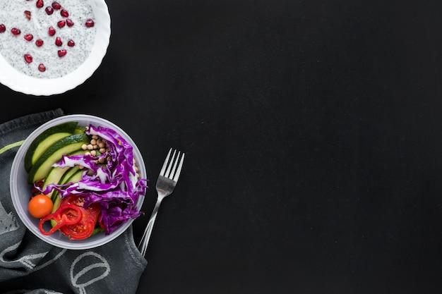 Een bovenaanzicht van chia zaad pudding en verse groenten salade op zwarte achtergrond