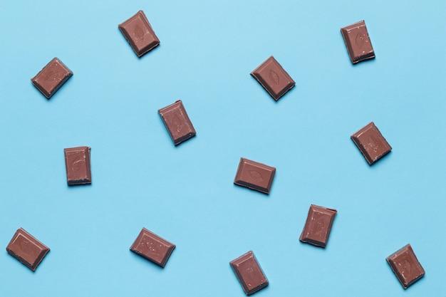 Een bovenaanzicht van chocoladestukjes op blauwe achtergrond