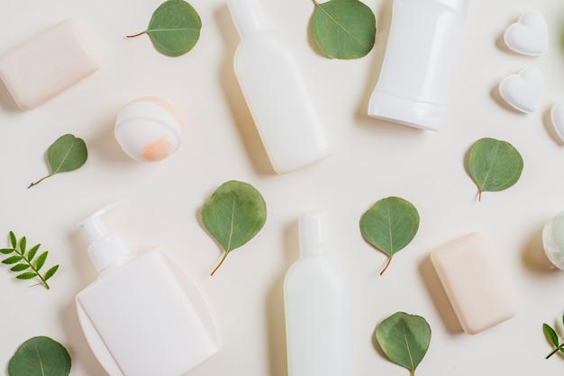Een bovenaanzicht van cosmeticaproducten; zeep; bad bom en groene bladeren