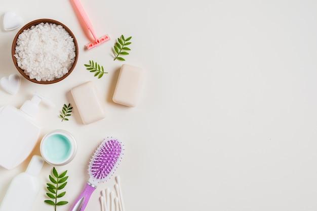 Een bovenaanzicht van cosmeticaproducten; zeep; scheermes oorknoppen en groene bladeren op witte achtergrond