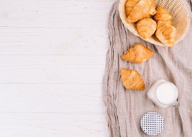 Een bovenaanzicht van croissants en melk in metselaar kruik op houten achtergrond