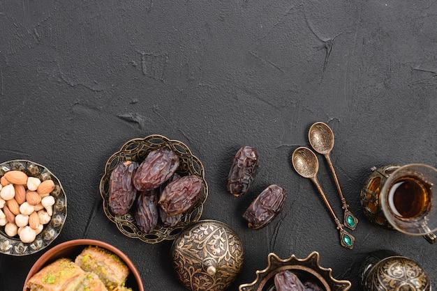 Een bovenaanzicht van datums in de traditionele turkse metalen kom; lepels en theeglazen op zwarte achtergrond
