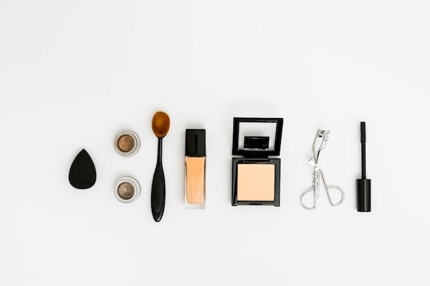 Een bovenaanzicht van de blender; oogschaduw; ovale borstel; compact poeder; wimperkruller en mascaraborstel op witte achtergrond