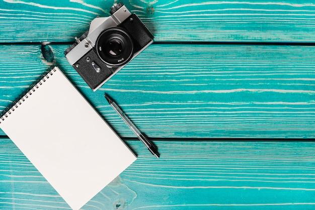 Een bovenaanzicht van de camera; spiraal kladblok en pen op houten plank