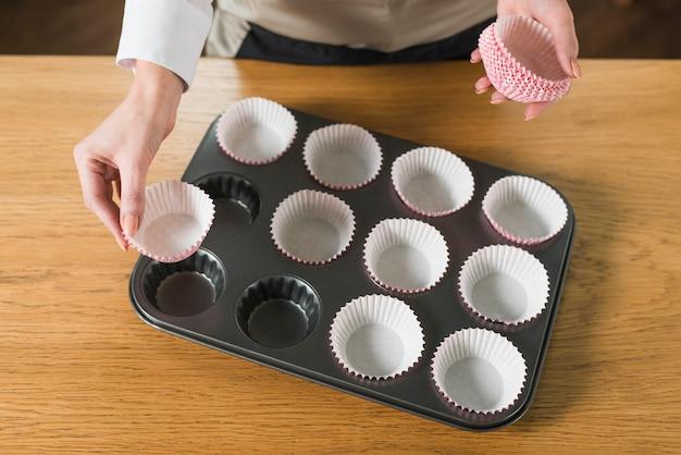 Een bovenaanzicht van de hand die van de vrouw cupcake houder in het bakplaat op houten tafel schikken