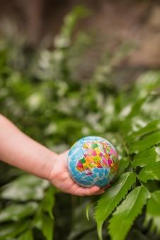 Een bovenaanzicht van de hand met globe bal over de groene plant