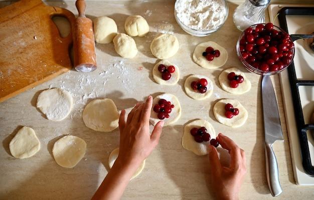 Een bovenaanzicht van de handen van een banketbakker die kersen op gerolde ronde deegvormen plaatst als een van de fasen van het maken van traditionele veganistische lekkere zoete knoedels