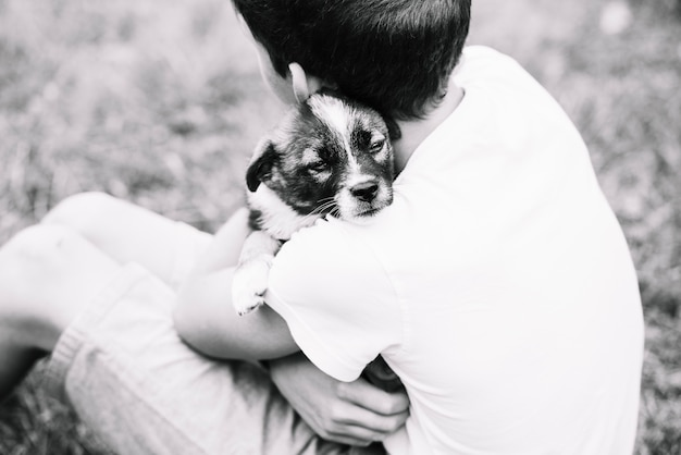Een bovenaanzicht van de jongen omarmen zijn mooie puppy