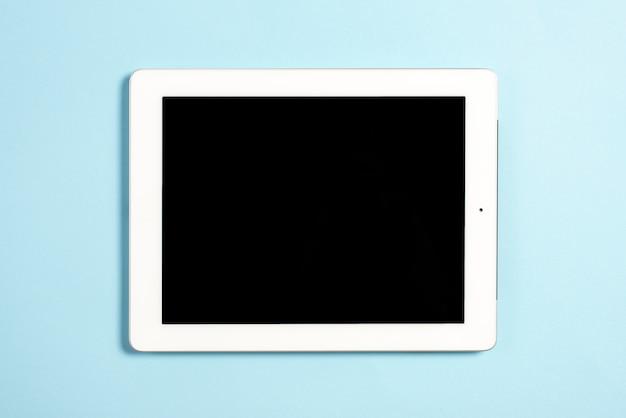 Een bovenaanzicht van digitale tablet met leeg scherm op blauwe achtergrond