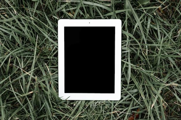 Een bovenaanzicht van digitale tablet met zwart scherm op groen gras