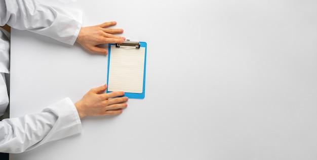 Een bovenaanzicht van doktershanden die een vel papier vasthouden om het recept voor de cliënt in het ziekenhuis op te schrijven