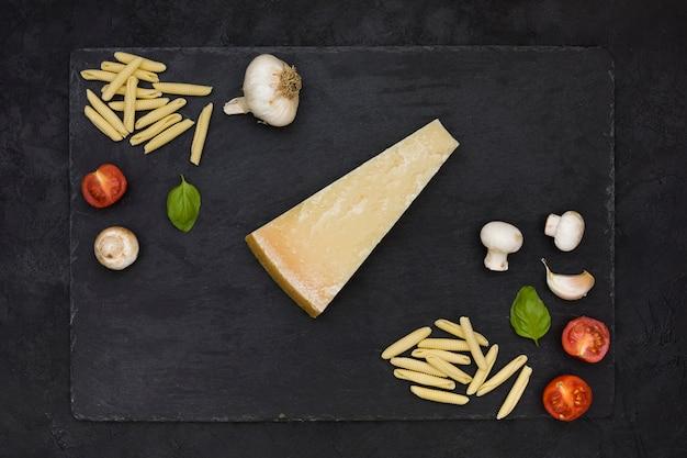 Een bovenaanzicht van driehoekig kaasblok met garganelli-pasta; paddestoel; knoflook; basilicum en tomaten op leisteen rock over de zwarte achtergrond