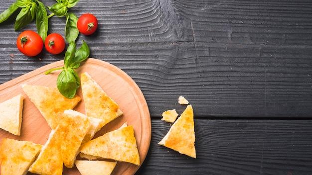 Een bovenaanzicht van driehoekige stukken brood met basilicumbladeren en tomaten