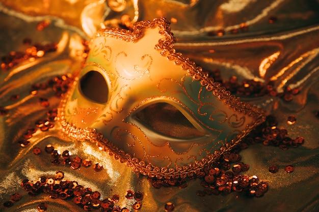 Een bovenaanzicht van een elegant gouden venetiaans masker op gouden textiel met pailletten