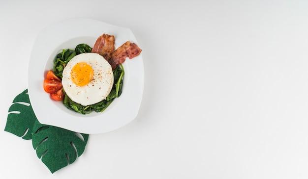Een bovenaanzicht van een gebakken ei met spinazie; tomaat en spek op witte plaat tegen een witte achtergrond