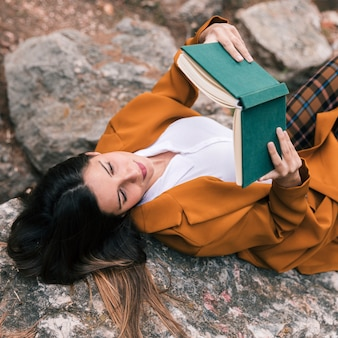 Een bovenaanzicht van een jonge vrouw liggend op het boek van de rotslezing