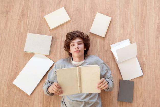 Een bovenaanzicht van een jongen tiener die op de vloer ligt en boeken leest, leert en studeert