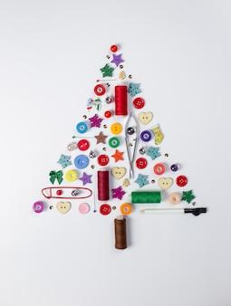 Een bovenaanzicht van een kerstboom gemaakt van kleurrijke naai-accessoires, knopen, spelden, naaigaren